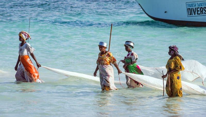 Nungwi, Zanzibar, Tanzania, Oost-Afrika - Juni 23, 2017: Afrikaanse vrouwen van een visserijdorp om kleine vissennetten in ocea t stock fotografie