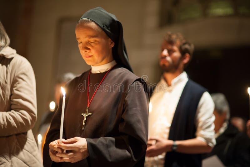Nunna som ber med stearinljuset royaltyfri foto