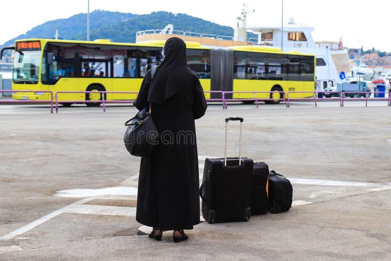 Nunna som reser med resväskor och bagage En kvinna i svart kloster- kläder väntar på en buss på stranden av arkivfoto