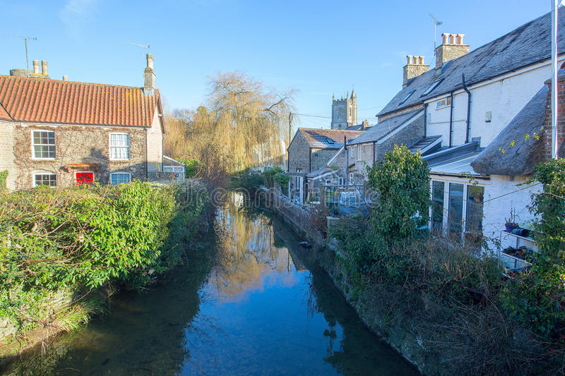 Nunney Brook and Church. View of Nunney brook in the village of Nunney Somerset looking upstream towards the 12th century parish church of All Saints royalty free stock images