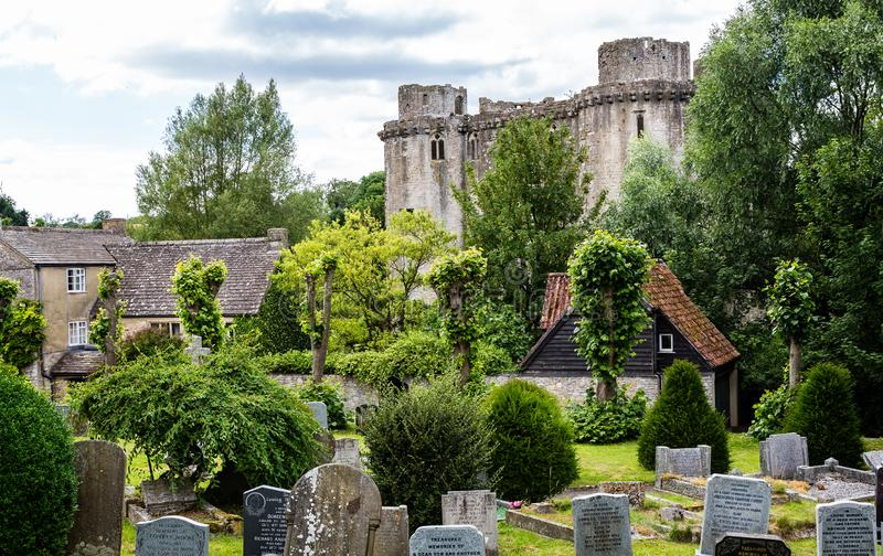 Nunney Castle with church grave yard in the foreground in Nunney, Somerset, UK. On 13 July 2014 royalty free stock image