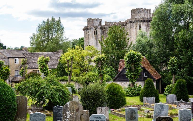 Nunneykasteel met kerk ernstige werf in de voorgrond in Nunney, Somerset, het UK royalty-vrije stock afbeelding