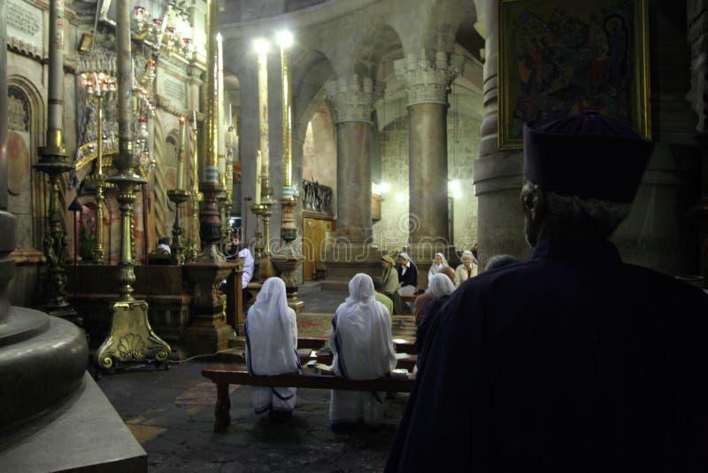 Nunnor som ber i kyrkan av den heliga griften i Jerusalem arkivfoto