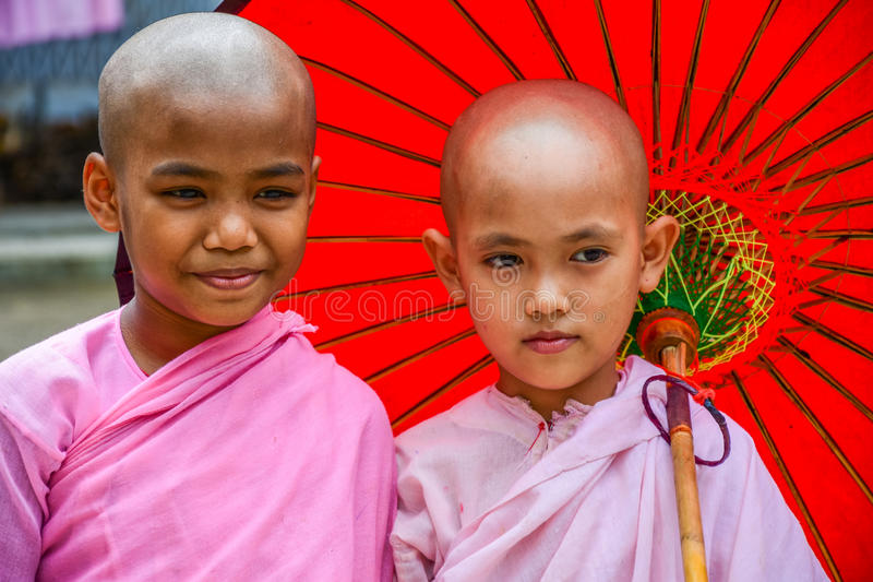 Nuns in pink robes with red paper umbrella royalty free stock images