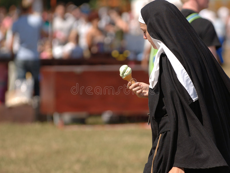 Nuns on the Run. A Nun eating an ice cream whilst walking royalty free stock photography