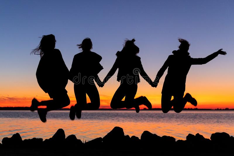 Silhouette of happy girls friends jumping in the air holding hands during sunset stock photo