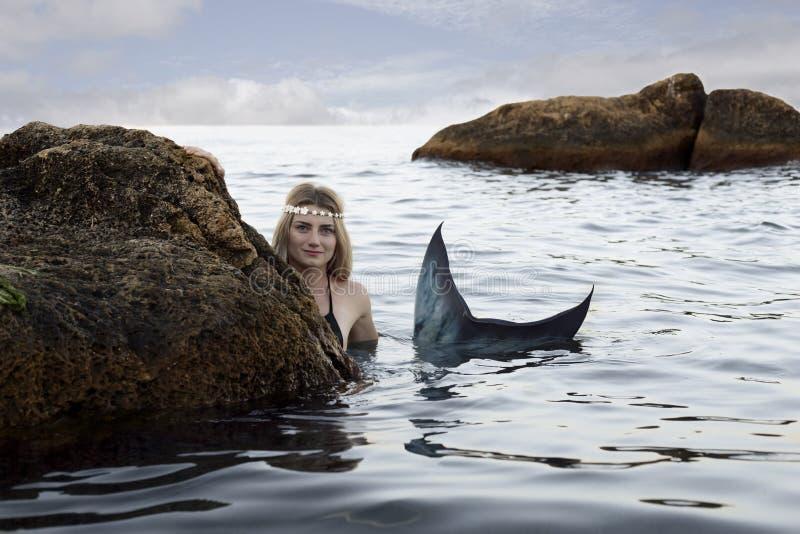 Nuotate della sirena nell'acqua che dà una occhiata dalle rocce fotografia stock libera da diritti