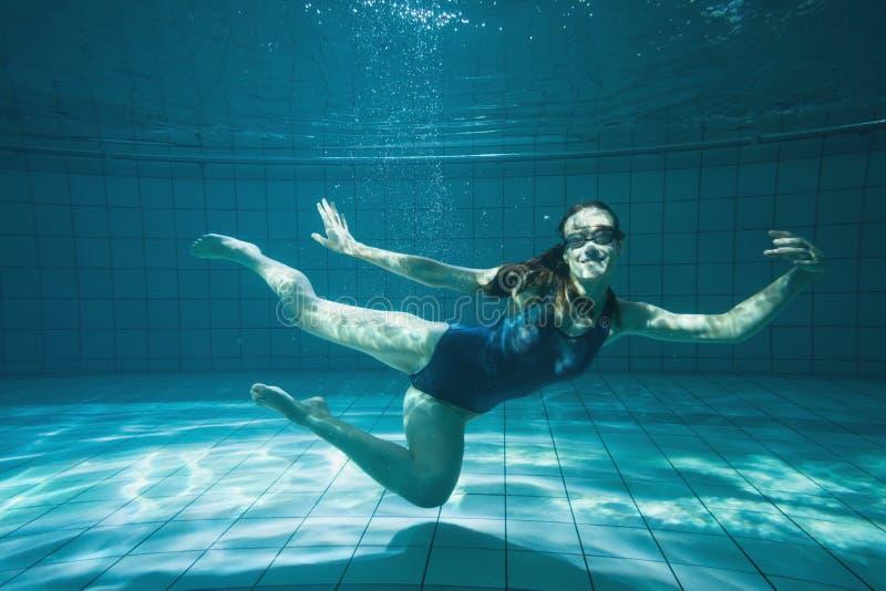 Nuotatore atletico che sorride alla macchina fotografica underwater immagine stock