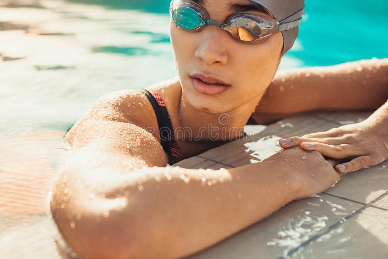 Nuotatore femminile che riposa dopo una nuotata immagine stock libera da diritti