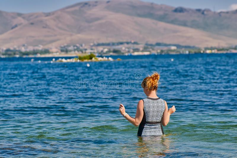 Nuoto andante della giovane donna nel lago Sevan dell'Armenia fotografia stock