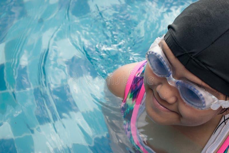 Nuoto asiatico di pratica della bambina per la partita nella piscina Bambina allegra in questa attività Pratica duro nuotare la b immagini stock libere da diritti