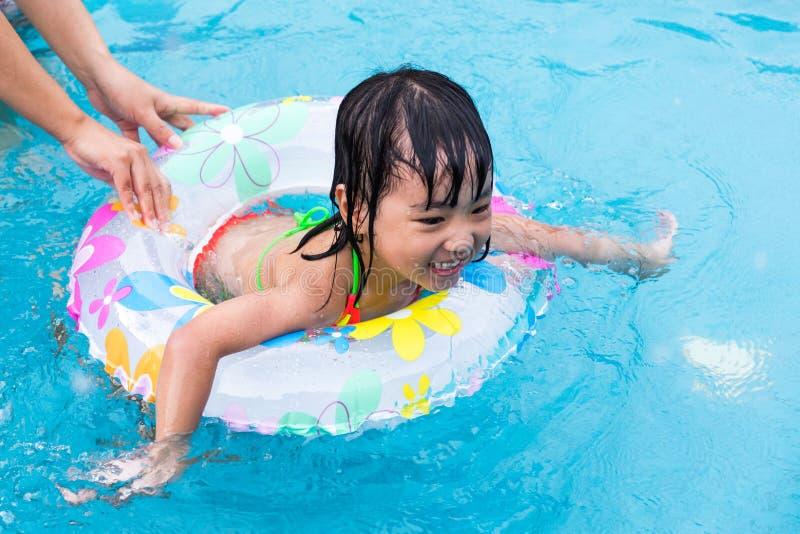 Nuoto d'istruzione della bambina della mamma cinese asiatica allo stagno immagine stock