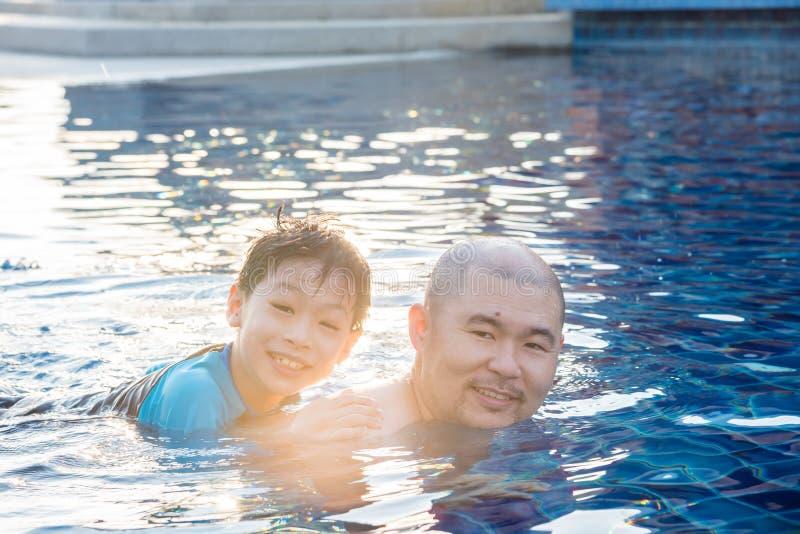Nuoto del figlio e del padre nello stagno insieme fotografia stock