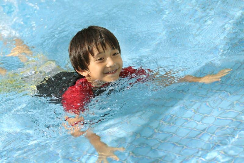 Nuoto del ragazzo nel raggruppamento immagine stock