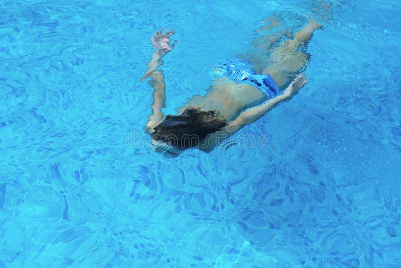 Nuoto del ragazzo sotto l'acqua fotografia stock