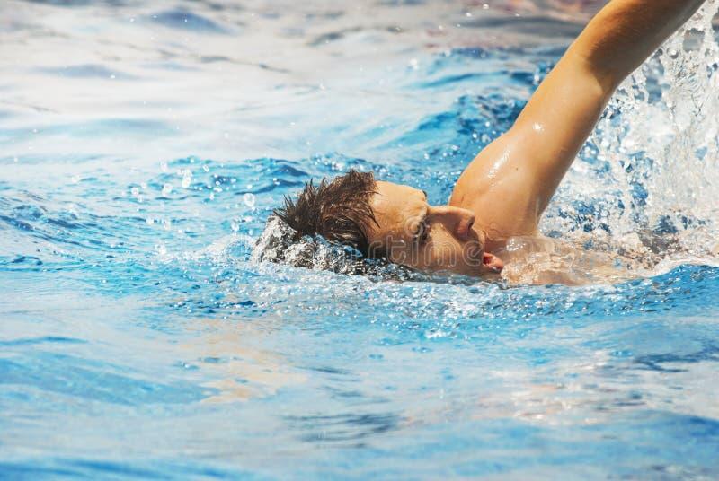 Nuoto del treno del nuotatore del giovane nella piscina fotografia stock