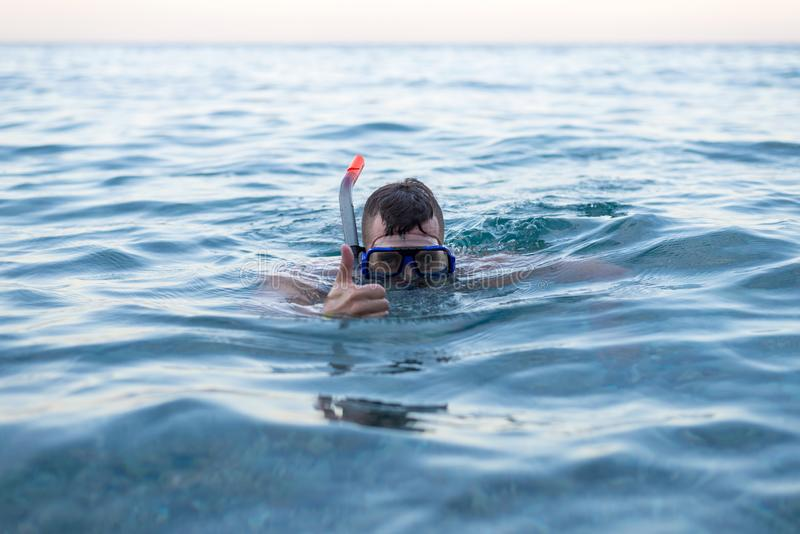 Nuoto dell'uomo in una maschera per l'immersione e la mostra del segno approssimativamente immagine stock libera da diritti