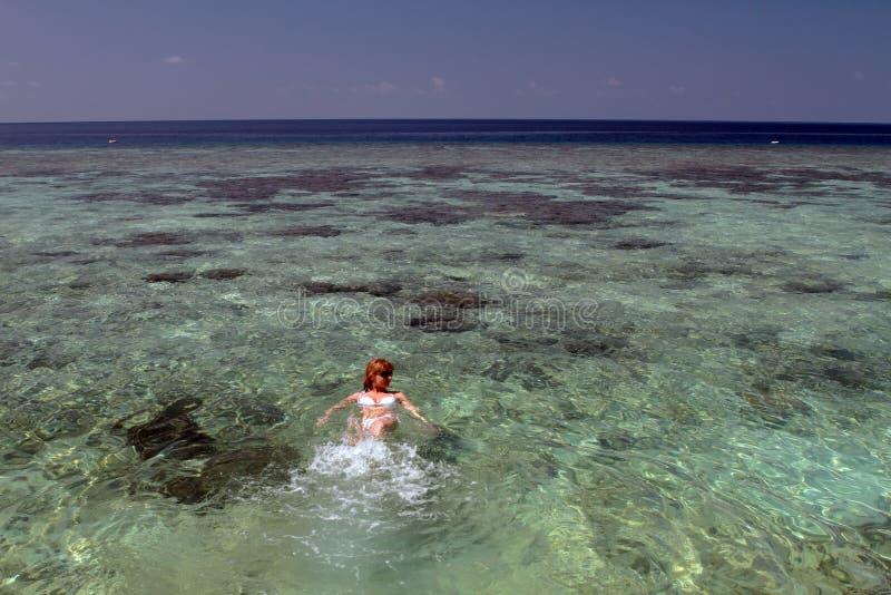 Nuoto della donna in Maldive fotografia stock libera da diritti
