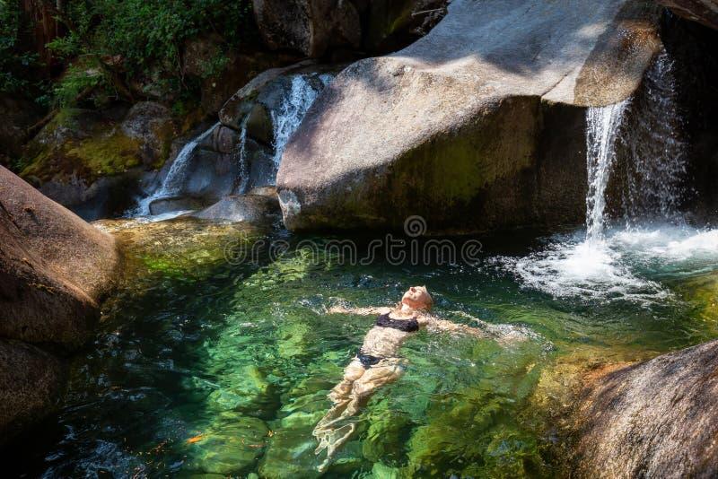 Nuoto della donna in un fiume del ghiacciaio fotografia stock