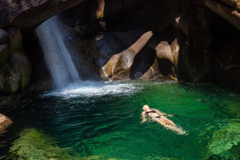 Nuoto della donna in un fiume del ghiacciaio fotografia stock libera da diritti