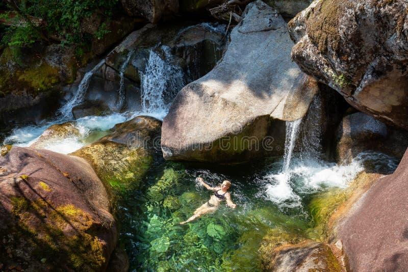 Nuoto della donna in un fiume del ghiacciaio immagine stock
