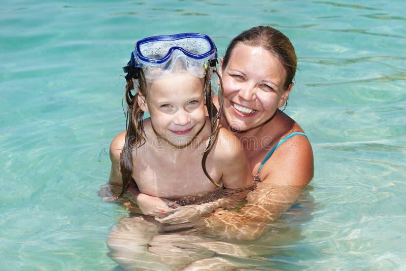 Nuoto felice della figlia e della mamma in acqua blu immagini stock libere da diritti