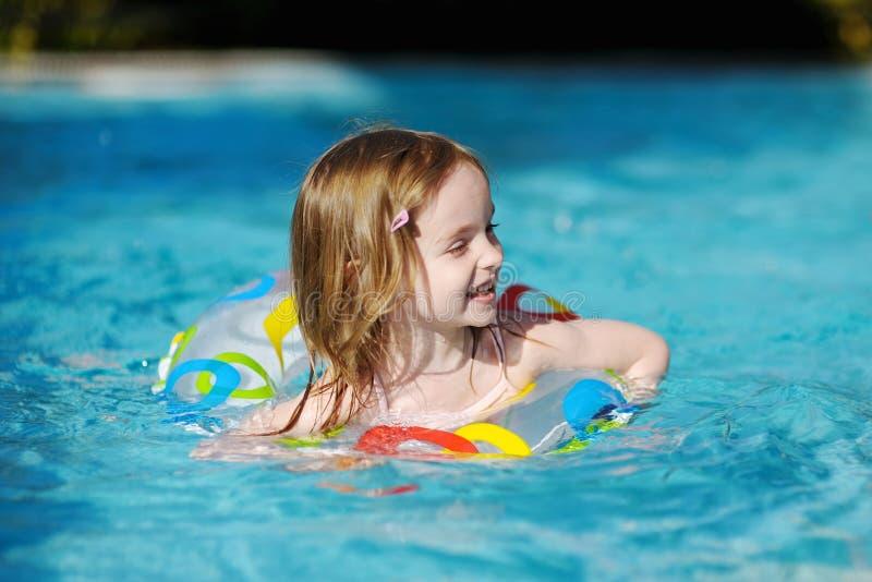 Nuoto grazioso della bambina in un raggruppamento immagine stock