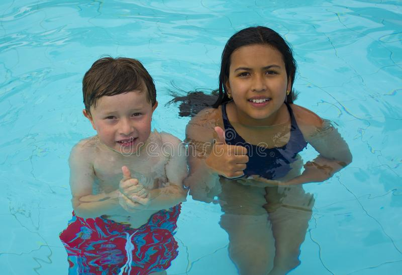 Nuoto sorridente della bambina e del ragazzo fotografia stock libera da diritti