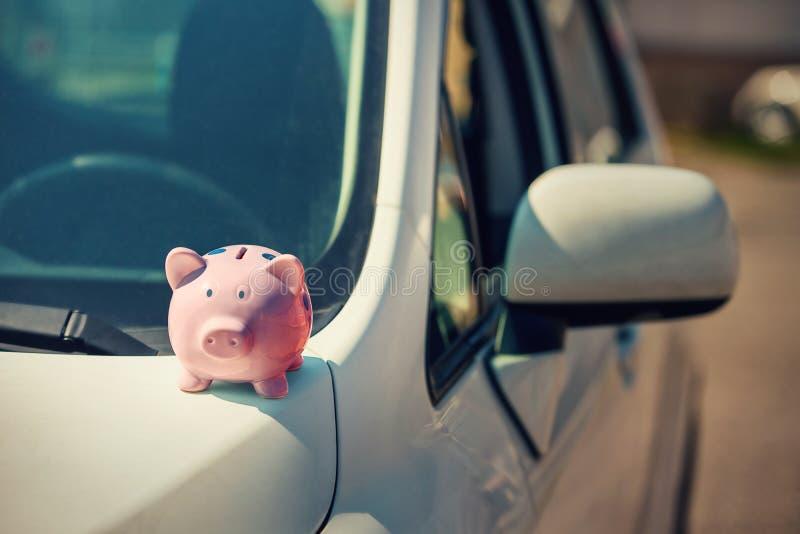 Nuova automobile con la banca rosa dei soldi di porcellino sul cappuccio Successo economico, assicurazione di beni immagine stock libera da diritti