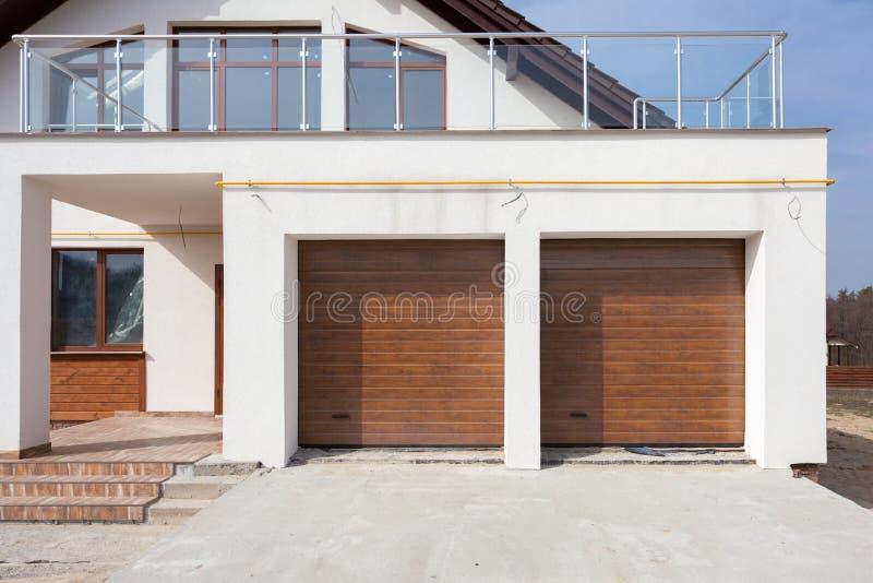 Nuova casa bianca con le doppi porte e balcone del garage immagini stock