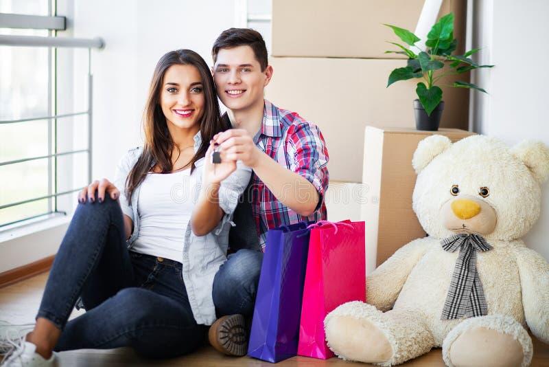 Nuova casa Le giovani coppie divertenti godono di e celebrando muoversi verso la nuova casa Coppie felici a stanza vuota di nuova immagine stock