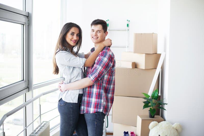 Nuova casa Le giovani coppie divertenti godono di e celebrando muoversi verso la nuova casa Coppie felici a stanza vuota di nuova immagini stock
