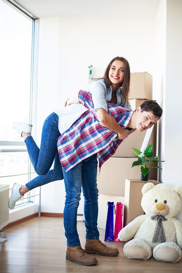 Nuova casa Le giovani coppie divertenti godono di e celebrando muoversi verso la nuova casa Coppie felici a stanza vuota di nuova immagine stock libera da diritti