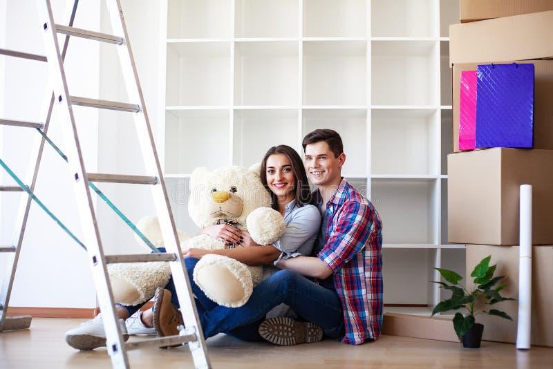 Nuova casa Le giovani coppie divertenti godono di e celebrando muoversi verso la nuova casa Coppie felici a stanza vuota di nuova immagini stock libere da diritti