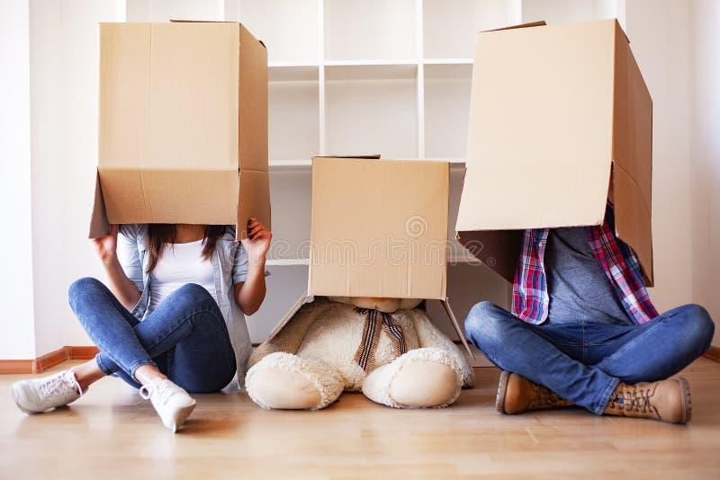 Nuova casa Le giovani coppie divertenti godono di e celebrando muoversi verso la nuova casa Coppie felici a stanza vuota di nuova fotografia stock
