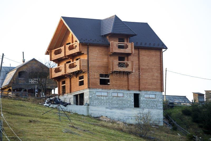 Nuova casa tradizionale ecologica di legno del cottage dei materiali naturali del legname con il tetto dell'assicella ed il semin fotografia stock