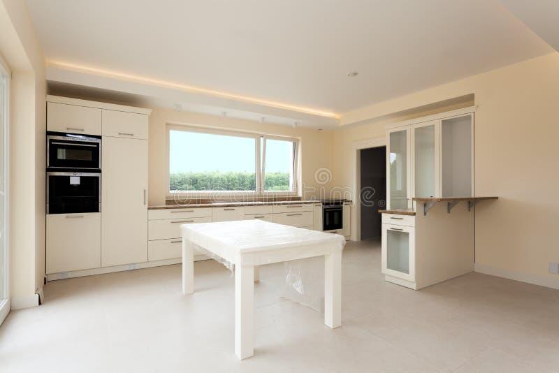 Nuova cucina con mobilia luminosa immagine stock