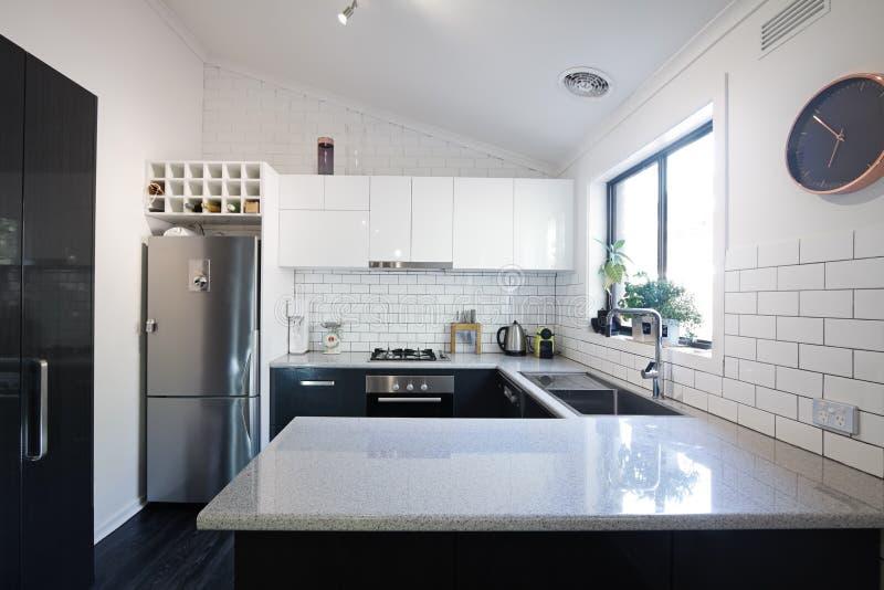 Nuova cucina contemporanea in bianco e nero con le mattonelle del sottopassaggio immagine stock libera da diritti