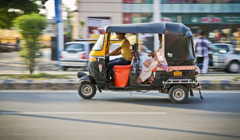 Nuova Delhi, India - 20 possono 2018: cottura di giovane driver indiano del risciò nella via con il passeggero in sari tradiziona fotografia stock