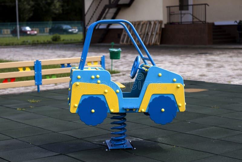 Nuova grande automobile blu e gialla variopinta luminosa di plastica moderna del giocattolo sulla molla del campo da giuoco della immagine stock