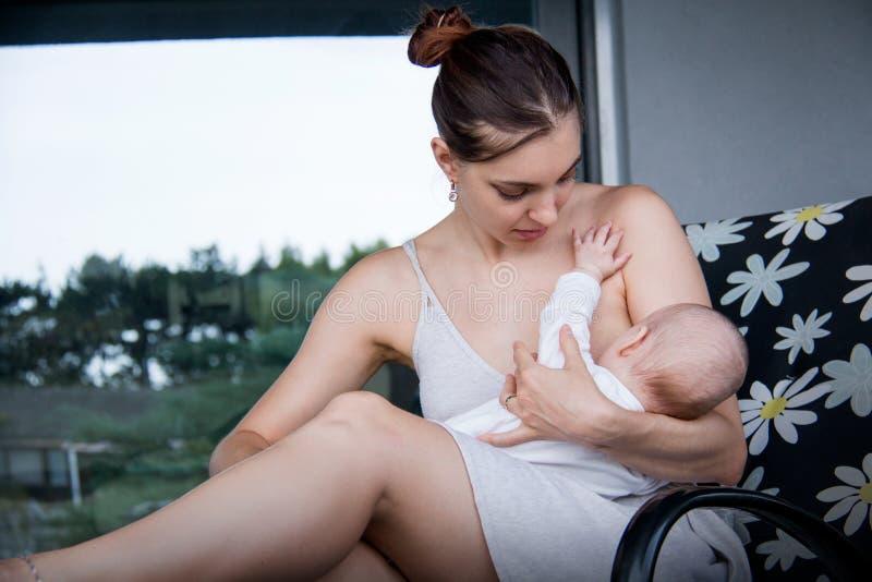 Nuova mamma che tiene il suoi piccoli figlio e allattamento al seno, bambino di cura immagini stock