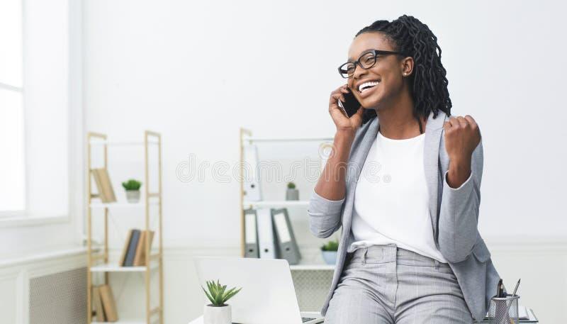 Nuova opportunità di lavoro Donna africana emozionante che parla sul telefono fotografie stock libere da diritti