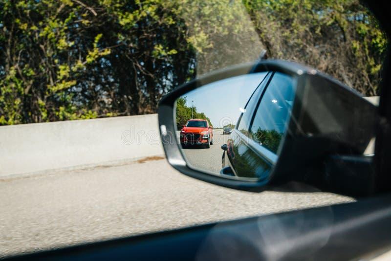 Nuova riflessione rossa di Hyundai Tucson SUV nella retrovisione dell'automobile fotografia stock libera da diritti