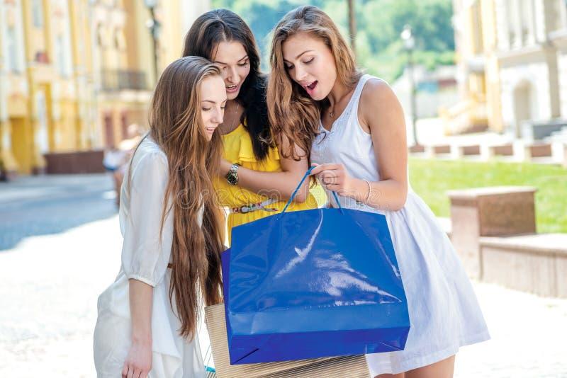 Nuove attrezzature Ragazze che tengono i sacchetti della spesa e passeggiata ai negozi fotografie stock