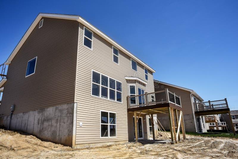 Nuove case a due piani in costruzione parzialmente finite nella suddivisione con il raccordo del vinile e finestre installati e n fotografie stock