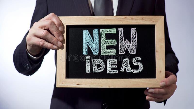 Nuove idee scritte sulla lavagna, segno maschio di concetto di affari della tenuta, motivazione immagini stock