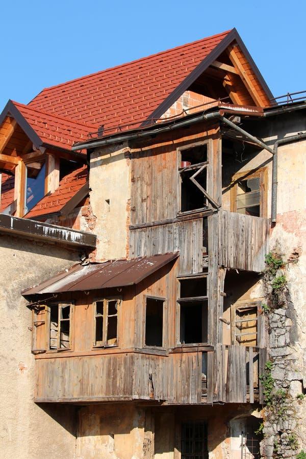 Nuove mattonelle di tetto sopra la casa nuovissima dei mattoni rossi con la vecchia multi casa livellata rotta di legno abbandona immagini stock