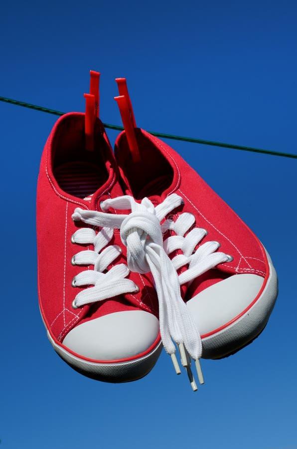 Nuove scarpe da tennis rosse sulla riga di lavaggio immagine stock libera da diritti