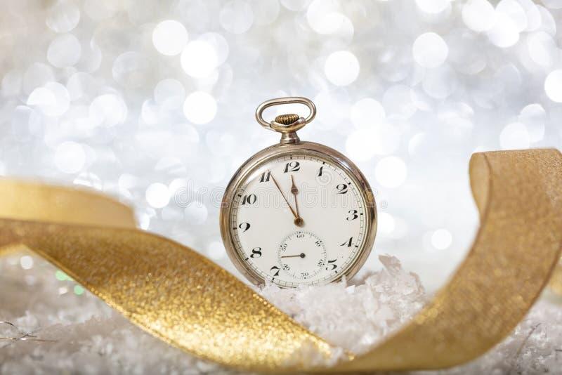 Nuovi anni di conto alla rovescia di vigilia Resoconto alla mezzanotte su un vecchio orologio, bokeh festivo fotografia stock