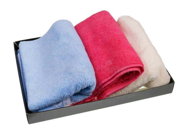 Nuovi asciugamani di bagno colorati di Terry in una scatola di cartone isolata immagine stock